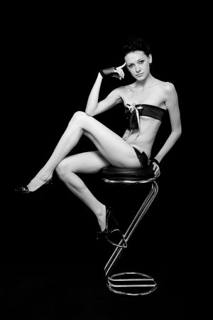 Black and white portrait of sexy woman, sitting on a chair on a black background photo