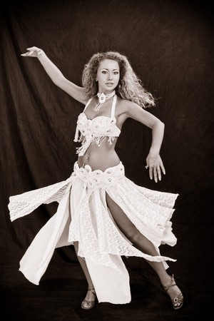 Belly dancer. Attractive girl in white dress on a black background. Stock Photo - 7636894