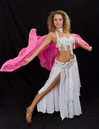 Belly dancer. Attractive girl in white dress on a black background. Stock Photo - 7636892