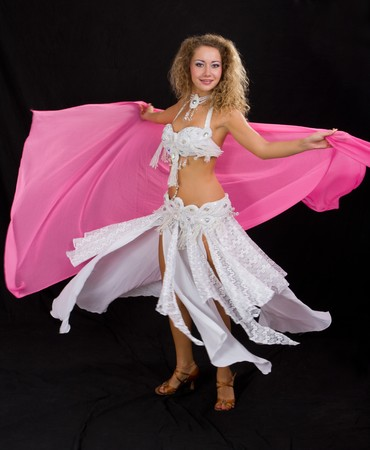 Belly dancer. Attractive girl in white dress on a black background. photo