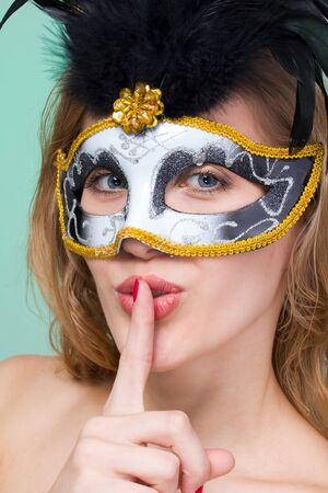 hush hush: Woman in carnival mask making silence gesture