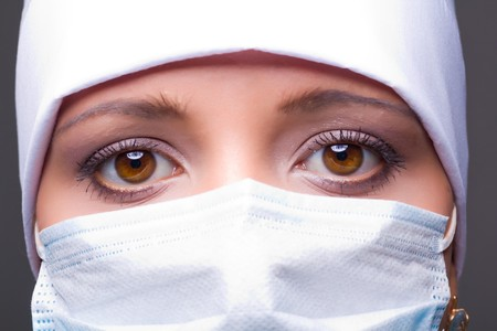 surgical cap: Closeup portrait of a young doctor wearing a mask Stock Photo