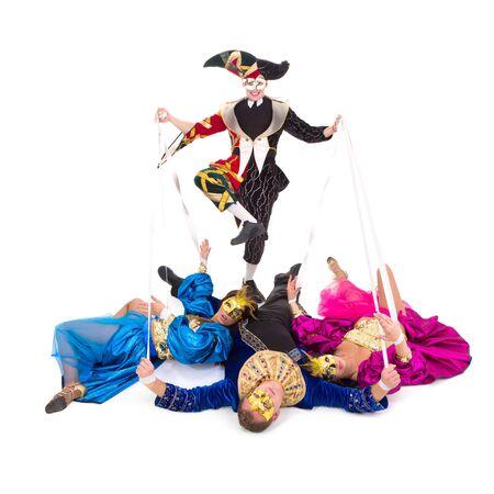 arlecchino: Arlecchino e marionette. Ballerini in costumi di Carnevale che posano su uno sfondo bianco  Archivio Fotografico