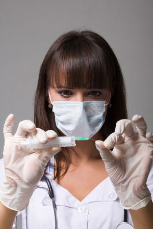 Young doctor wearing a mask with syringe on a grey background photo