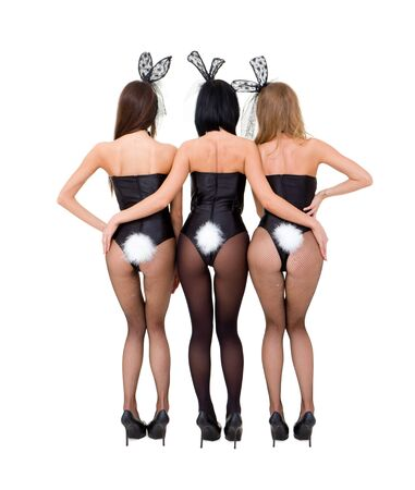 Sexy playgirls wearing a bunny costumes posing against isolated white background Stock Photo