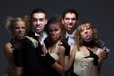 Portrait of hungry vampire family on a gray background photo