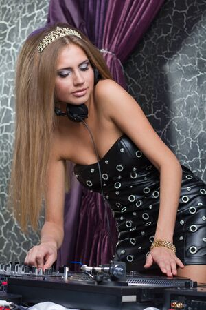 Beautiful and sexy DJ girl on decks on the party photo