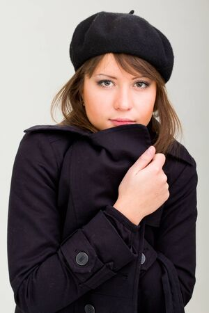 woman wearing in a coat and beret on a gray background photo