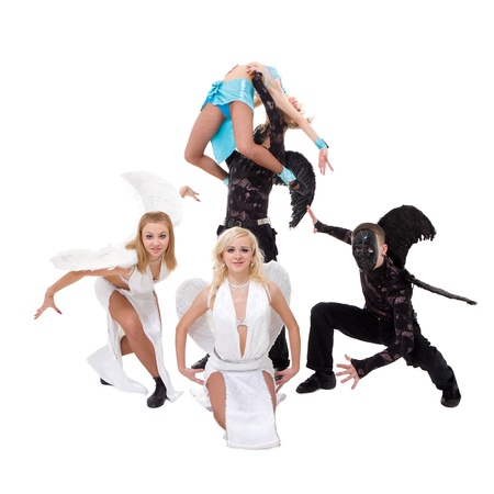 Dance team dressed as angels and demons dancing against isolated white background photo