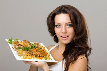 smiling young woman posing with a meal on a gray background Stock Photo - 9040848