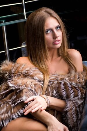 Attractive young woman wearing a fur coat photo