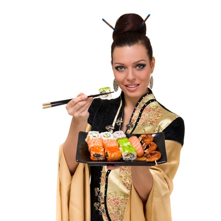 Woman wearing a traditional dress eating sushi, isolated on white background  Stock Photo - 15531570