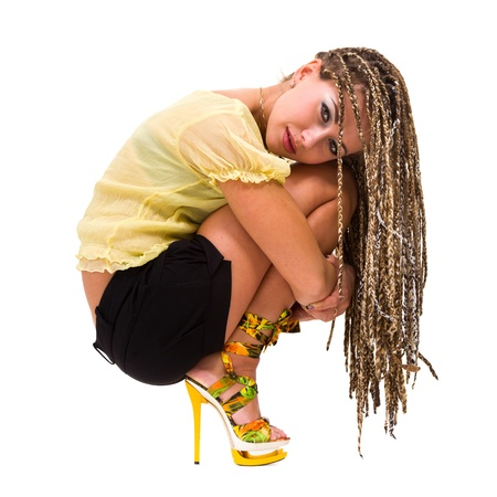 Beautiful young woman with dreadlocks siiting against isolated white background