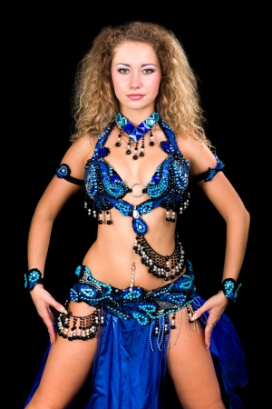 Belly dancer  Attractive girl in blue dress on a black background  photo
