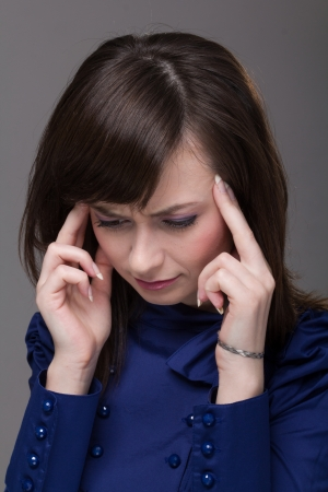 young woman with headache on a gray background Stock Photo - 15843304