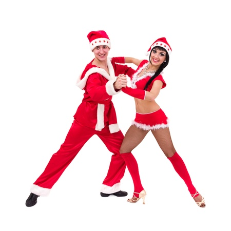 Happy young couple wearing santa claus clothes posing against isolated white background photo