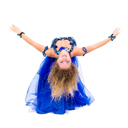 Attractive belly dancer dressed in a blue costume dancing against isolated white background photo