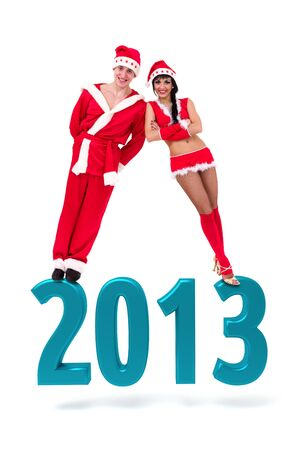 Happy young couple wearing santa claus clothes on a 2013 New Year sign, isolated on white photo
