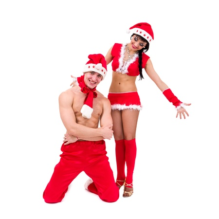 Happy young couple wearing santa claus clothes posing against isolated white background Stock Photo