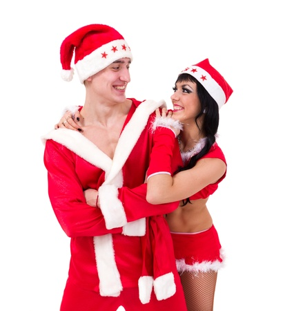 Happy young couple wearing santa claus clothes, against isolated white background photo