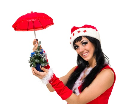 girl wearing santa claus clothes with an umbrella and Christmas tree posing against isolated white background photo