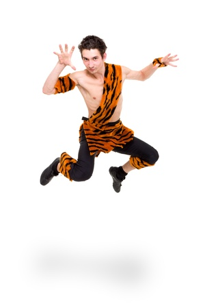 Wild man wearing a tiger skin jumping against isolated white background photo