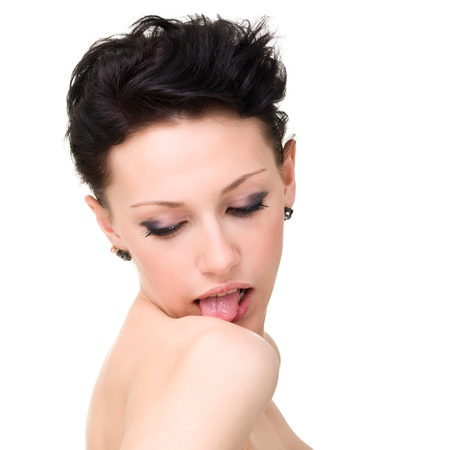 Young woman licking her shoulder. Isolated over white background with copy space. photo