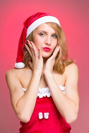 Close-up portrait of young woman wearing santa claus clothes on a red background photo