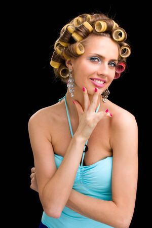 portrait of young beautiful woman having hair curlers on her head isolated on black background Stock Photo - 16754173