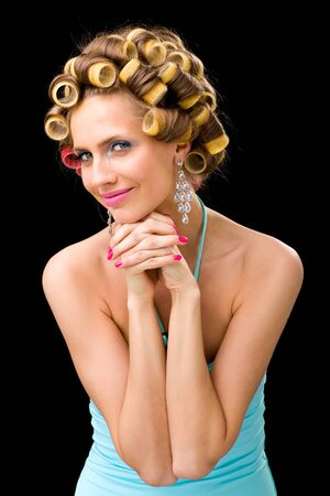 portrait of young beautiful woman having hair curlers on her head isolated on black background photo