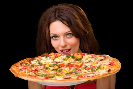 young woman eating a pizza against a black background Standard-Bild