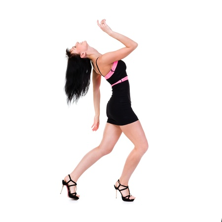 Full length of  sensual woman wearing a little black dress dancing against isolated white background photo