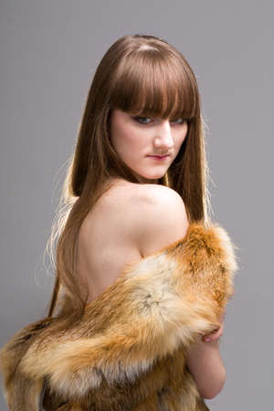 woman wearing a fox fur on a gray background photo