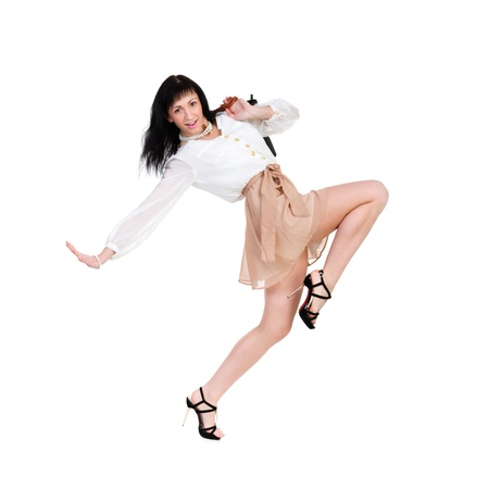 Full length of  sensual woman in short skirt dancing against isolated white background photo