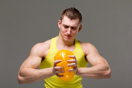 arm muscles: Muscular young man flexing arm muscles on gray background