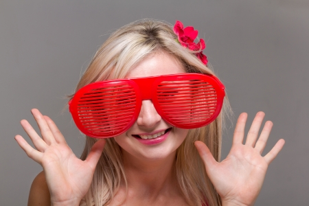 Woman in crazy clown glasses on gray