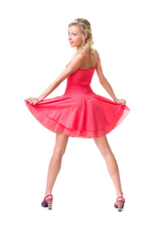 Full length of  sensual woman in short dress dancing against isolated white background photo
