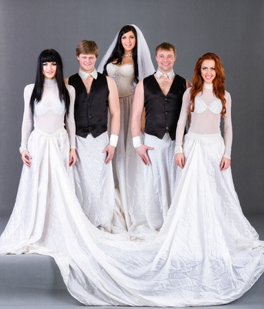Actors in the wedding dress posing  On a gray background in full length  photo