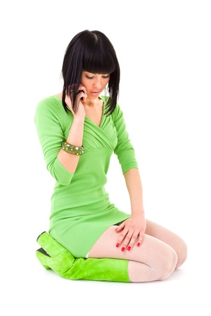 woman sitting and phoned in a short dress studio portrait isolated on white photo