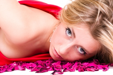shot of sexy woman in red dress with rose petals, isolated on white background photo