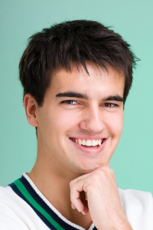 Handsome young man with a charming smile - isolated on green photo