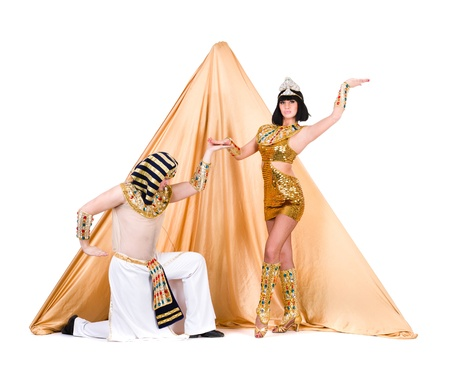 dance team dressed in Egyptian costumes posing against of stylized pyramid   Isolated on white background in full length  photo