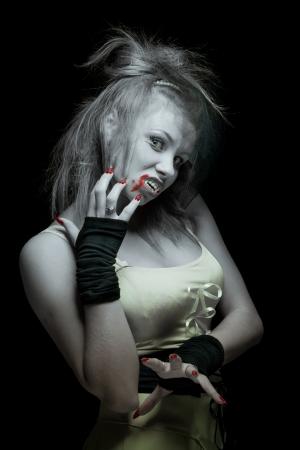 retrato de una mujer vampiro con colmillos sobre un fondo negro photo