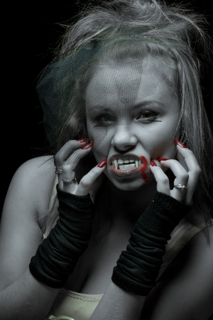 portrait of a woman vampire with fangs on a black background photo