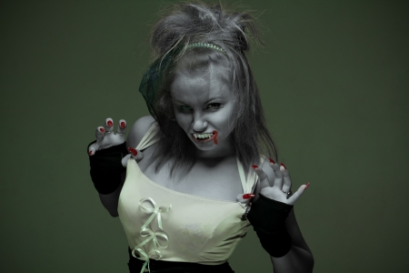 portrait of a woman vampire with fangs on a dark background photo