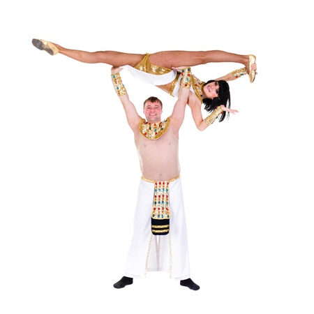 acrobatic dance couple wearing a egyptian costume doing splits against isolated white background photo