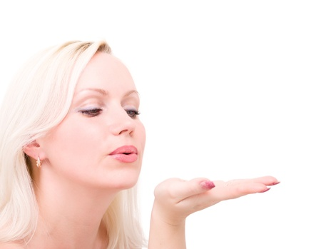blow kiss: Young blonde woman blowing while sending an air kiss against a white background Stock Photo