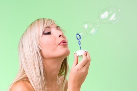 Beautiful young woman blowing soap bubbles  isolated on green photo