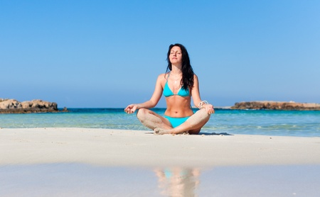 Peaceful healthy fit young woman meditating on the beach photo