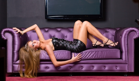 alluring woman wearing a short dress relaxing on a sofa photo